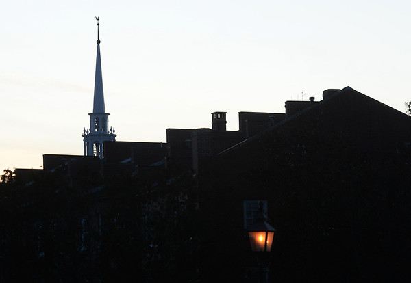 BRYAN EATON/Staff Photo. The setting sun highlight the geometric shapes in downtown Newburyport like chimneys, firewalls and the Unitarian Church's steeple.