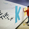 "BRYAN EATON/Staff Photo. Amesbury's Cashman Elementary School third-graders Elijah Bartosik, 8, left, and Emmy Kmiec, 9, take their turns signing the ""Be the I in KIND"" mural for World Kindness Day on Wednesday. The day also honors Fred Rogers of Mr. Rogers Neighborhood and staff wore cardigan sweaters to mark the occasion."