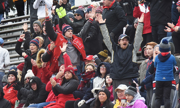 BRYAN EATON/Staff Photo. Fans bundled up for the rain and raw weather cheer on their respective teams at the Thanksgiving Day football game.