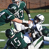BRYAN EATON/Staff photo. Pentucket defenders take down Swampscott's Xaviah Bascon after a catch.