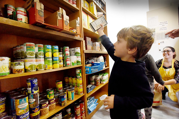 BRYAN EATON/Staff Photo. Connor Mandeville, 3, puts away soup stock at the Newbury Community Food Pantry.