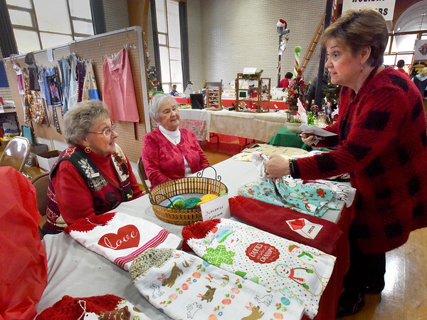 BRYAN EATON/Staff photo. Joyce Meekins of Amesbury checks out handmade kitchen towels at a booth manned by Mary Ellen Emmells, left, and Denis Pilon, both of Amesbury, where they were also selling handmade baby bibs and scrubbies made by Pilon at the Holy Family Parish Hall.