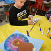 BRYAN EATON/Staff Photo. Declan Gibbon, 5, colors a coffee filter in Carol Jakobsons' kindergarten class which he will roll up and dip in water where the colors will bleed like tie dye art. When opened and dried it will create a turkey's tail feathers as in the artwork in foreground.