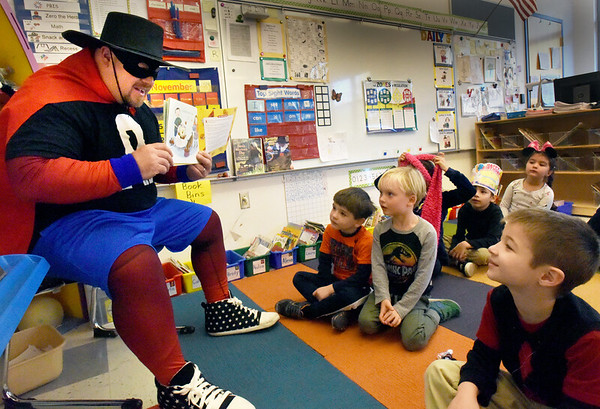 "BRYAN EATON/Staff Photo. Zero the Hero, a.k.a. Ken Parseghian, reads the book ""Give Me Half"" which teaches youngsters to share a pizza using fractions at the Bresnahan School. The caped hero teaches the kindergartners to teach them about zero and get them excited about math every 10 days and was here on the 50th day of school. On the 100th day of school he arrives in a police cruiser and the children have a party with cupcakes with the number 100 decorating the top."