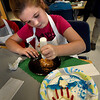 BRYAN EATON/Staff Photo. Bella Eaton, 9, puts the lacing on a football cookie after decorating a patriotic-themed cookie in foreground for Veterans's Day. She was in the afterschool Explorations program Crazy for Cookies at Salisbury Elementary School.