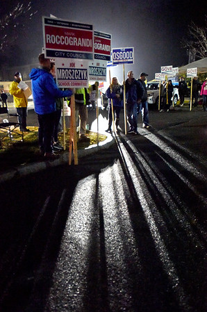 BRYAN EATON/Staff Photo. Floodlights cast shadows of pollsters greeting voters to Amesbury High School on Tuesday night to cast ballots for mayor and other races.
