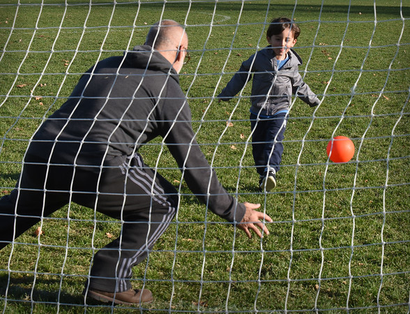 BRYAN EATON/Staff Photo. Luiz Peixoto, 4, of Salisbury kicks the soccer ball as his dad, Jose, plays goalie under a sunny sky at Cashman Park in Newburyport. Rain and possibly snow was forecast for Thursday night with temperatures cooling on Friday after a front goes through the region.