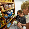 BRYAN EATON/Staff Photo. Food pantry director Jane Merrow helps Mariella Hull, 5, on where to put a box of corn.
