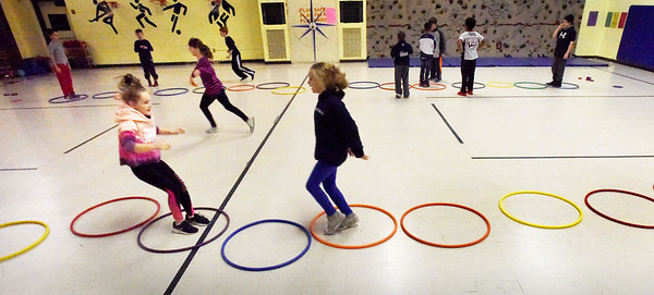 """BRYAN EATON/Staff photo. Youngsters play a game of """"hoop hop showdown"""" in Margaret Welch's physical education class at Amesbury Elementary School on Monday afternoon. A member from each team hops in the hula hoops and when they meet up do """"rock, paper, scissors"""" with the winner passing by. Whichever team has the most members return to their side wins."""