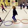 "BRYAN EATON/Staff photo. Youngsters play a game of ""hoop hop showdown"" in Margaret Welch's physical education class at Amesbury Elementary School on Monday afternoon. A member from each team hops in the hula hoops and when they meet up do ""rock, paper, scissors"" with the winner passing by. Whichever team has the most members return to their side wins."