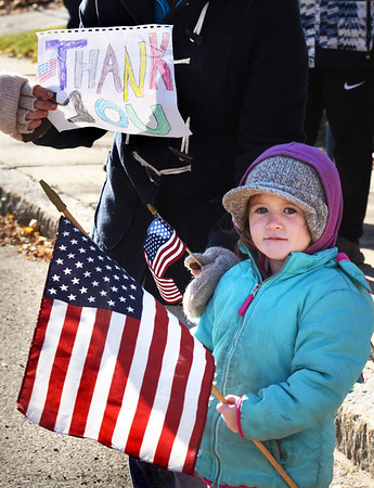 BRYAN EATON/Staff photo. Lydia D'Andrea, 3, holds flags as the parade goes by and her mom, Tanya Piercey, holds a sign saying thank you to veterans.