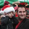 JIM VAIKNORAS/photo Oliver Madrosian, 3, covers his ears as the fire trucks goes by in Market Square at the Newburyport's annual parade and tree lighting. Oliver, along with his dad Brian, were there to light the tree, that was donated by their family.