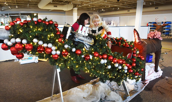 "BRYAN EATON/Staff photo. Meredith Flynn, left, Dracut and Marie Kostoulakos of Methuen work on their ""Santa's Got a Brand New Ride"" at the SeaFestival of Trees."