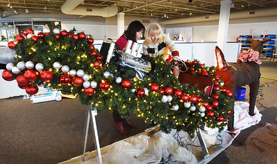 """BRYAN EATON/Staff photo. Meredith Flynn, left, Dracut and Marie Kostoulakos of Methuen work on their """"Santa's Got a Brand New Ride"""" at the SeaFestival of Trees."""
