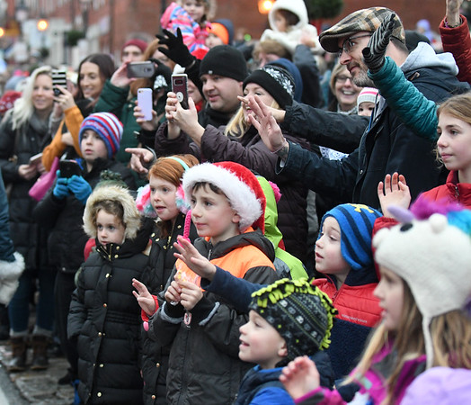 JIM VAIKNORAS/photo Kids and adults wave and take photos with their phones as Santa and Mrs. Claus make their way up State Street in Newburyport Sunday afternoon for the city's annual parade and tree lighting.