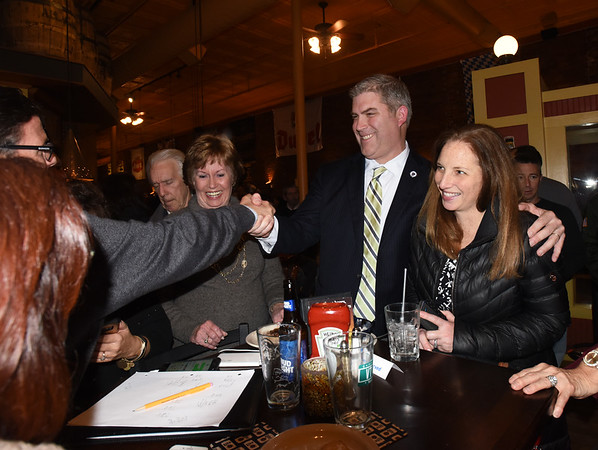 BRYAN EATON/Staff photo. Jim Kelcourse, with his wife Amanda, get congratulations on his re-election with supporters at the Alehouse in Amesbury on Tuesday night.