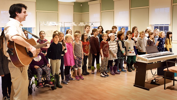"""BRYAN EATON/Staff photo. Bresnahan School Gardner Rulon-Miller leads students in several songs including """"Three Little Birds"""" by Bob Marley. They were performing at the annual meeting of Friends of the Newburyport Council on Aging which fund many of the senior center's programming."""