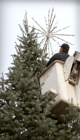 BRYAN EATON/Staff photo. Firefighter Patrick O'Loughlin is hoisted in a bucket to attach the star at the top of the tree.