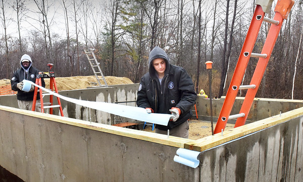 BRYAN EATON/Staff photo. Americorp members Andrew Kirk, left, and Nick McGrew measure out gasketing strip that reduces air draft between framing and the foundation at the Habitat For Humanity housing going up on Old County Road in Salisbury.