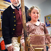 BRYAN EATON/Staff photo. Presenters from Historic New England were on hand for Colonial Day at the Cashman School in Amesbury on Tuesday, provided by the school's PTO, culminating their unit on Colonial America. Mike Welch looks over Gianna Leblanc, 8, as she turns a lever to make three strands from 12 of the plant fiber jute, used for rope-making, then others took turns combining those three into a single piece of sturdy rope.