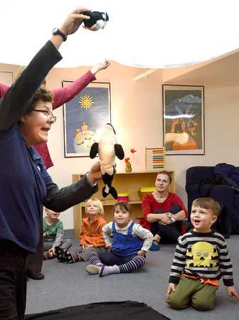 """BRYAN EATON/Staff photo. Lisa Hutchings from Audubon's  Joppa Flats Education Center brought the program """"Penguins To Go"""" to the Newburyport Montessori School on Tuesday morning. Here she shows how an orca whale hunting for a meal looks up but can't sea the penguin as its white underbelly blends in with the top of the ocean, represented by a white sheet."""