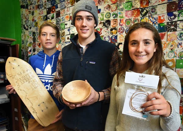 BRYAN EATON/Staff photo. Newburyport Youth Services is hosting its annual holiday craft show on November 28, pictured are some of the crafters. From left, Tommy Seidel, 14, with a skateboard, with wheels to be added; Matthew Reeves, 16, with a bowl carved from maple and Olivia Coletti, 16, and perfume necklaces.