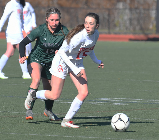 JIM VAIKNORAS/photo Amesbury's Maia Esty looks to clear the ball while guarded by  Mancester-Essex player Madison Lawler during their game at Manning Field in Lynn Sunday. Amesbury won the game 2-1 in double overtime.