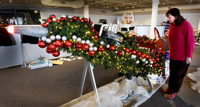 """BRYAN EATON/Staff photo. Meredith Flynn, right, of Dracut and Marie Kostoulakos of Methuen work on their """"Santa's Got a Brand New Ride"""" at the SeaFestival of Trees."""