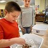 BRYAN EATON/Staff photo. Austin Palladino, 10, counts pennies into a boat he created out of aluminum foil sitting in a tub of water to see how many he can put in before it sinks as Heidi Sanger, 10, watches after testing out her design. They were in Newbury Elementary School's new Makerspace Room which is used for STEM (Science, Technology, Engineering and Mathematics) projects and was created using grant money from the Institution For Savings. Each week students are given a new challenge to work on using STEM's design cycle.