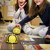BRYAN EATON/Staff photo. Skyler Montoya-Wakefield, 7, left, reacts as her BeeBot turns around as Isla Freeman, 6, sets hers down on the track in Kristin Spinney's STEM class at the Bresnahan School on Monday. Next week is National Computer Science Week where students around the country will learn coding on computers and this class got a headstart by practicing with the BeeBots which they coded to run the course a certain way by turning, right, left and reversing direction.