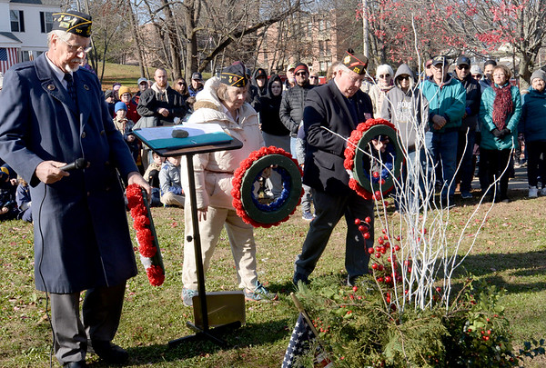 BRYAN EATON/Staff photo. Veterans place wreaths at the base of the Dougboy Statue, from left, Gary Eichenlaub, commander of Amesbury Legion Post 187, his wife, Mary, adjutant of the post, and Donald Robers, district commander of the VFW.