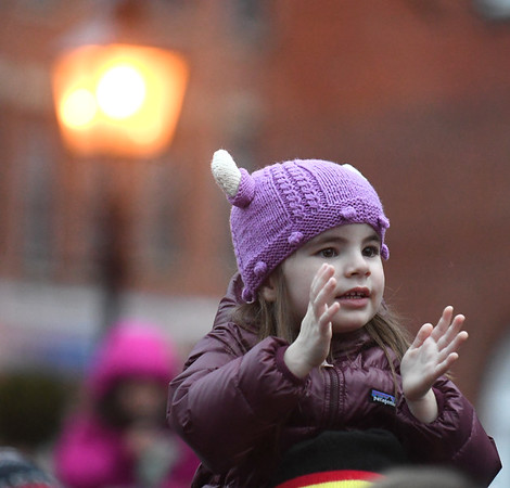JIM VAIKNORAS/photo A girl in a purple Viking hat claps along with Christmas music in Market Square in Newburyport Sunday afternoon during the city's annual parade and tree lighting.