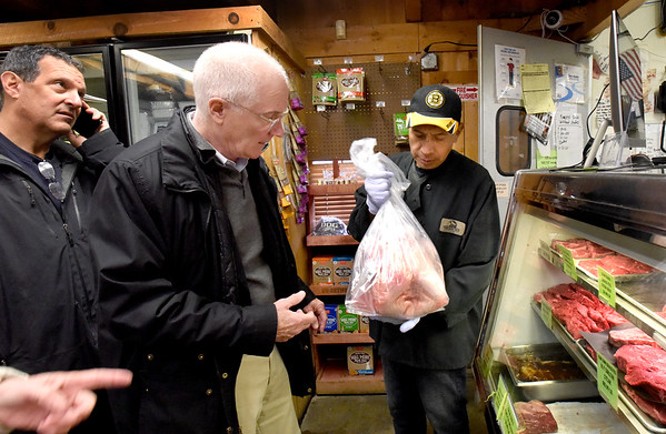 BRYAN EATON/Staff photo. Eddie Ventura hands John Forbes of Boxford his Thanksgiving Day turkey that he was in line 45 minutes for at Tendercrop Farm as their local turkeys and meats have become more popular over the years.