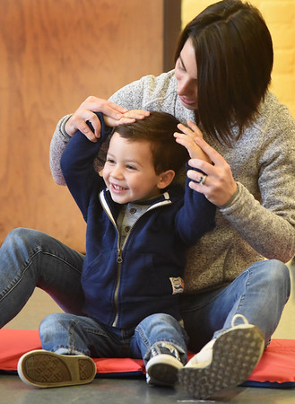 """BRYAN EATON/Staff photo. Andrew Scarsella, 3, of Merrimac laughs as his mother Jaclyn moves his hands around, tickling him on the way, during the song """"Little Mouse Goes Creeping"""" at the Newburyport Rec Center. Claudia Keyian brings her Music Rocks on most Wednesdays getting young children interested in music and interaction with each other in the program sponsored by Newburyport Youth Services."""