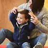 "BRYAN EATON/Staff photo. Andrew Scarsella, 3, of Merrimac laughs as his mother Jaclyn moves his hands around, tickling him on the way, during the song ""Little Mouse Goes Creeping"" at the Newburyport Rec Center. Claudia Keyian brings her Music Rocks on most Wednesdays getting young children interested in music and interaction with each other in the program sponsored by Newburyport Youth Services."