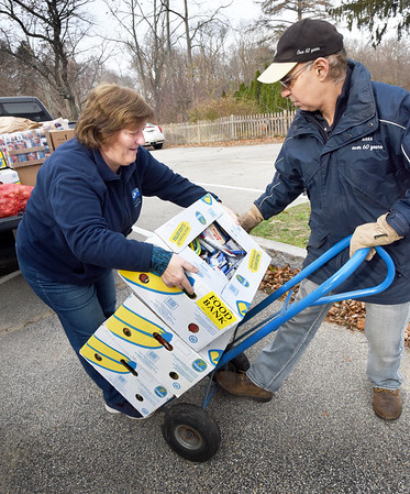 BRYAN EATON/Staff photo. Donna Fournier, left, and state Rep. Lenny Mirra move food off a truck from the Boston Food Bank at the First Parish Church of Newbury on Thursday morning. He was there to see and lend a hand to the Newbury Community Food Pantry, which is housed there, for distribution for Thanksgiving meals.