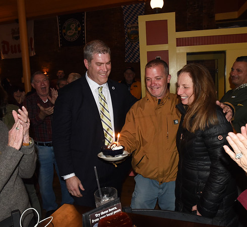 BRYAN EATON/Staff photo. Ron Lever brings a cake to state Rep. Jim Kelcourse and his wife Amanda celebrating their 8th wedding anniversary and a re-election win on the same night.