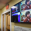 BRYAN EATON/Staff photo. Monitors show the programming at Port Media as  Drew Moholland interviews Newburyport Donna Holaday for the NCM Hub.