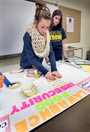 BRYAN EATON/Staff photo. Jamie Goss, 18, left, and Ruth Guilbault, 17, work on an informational poster about food insecurity, what it is and how the public can help.  The Amesbury HIgh School students are taking a writing class taught by Northern Essex Community college teacher Therea DeFranzo and are doing a service learning project which includes learning about food insecurity and conducting a food drive to help families affected by the gas explosions. They're working in conjunction with the Amesbury Public Library, which will be offering information about food insecurity and collecting dropoff items.