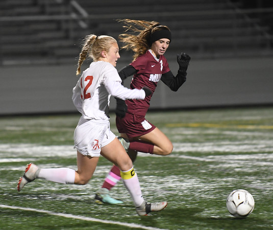 JIM VAIKNORAS/photo Amesbury's Chelsea Lynch races for the ball with Millis player Ciara Moynihan during their state semi-final game at Mansfield High School Wednesday. Amesbury lost the game 2-1.