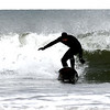 JIM VAIKNORAS/Staff photo A surfer braves the cold and wind to catches a wave off Seabrook Beach Saturday morning.