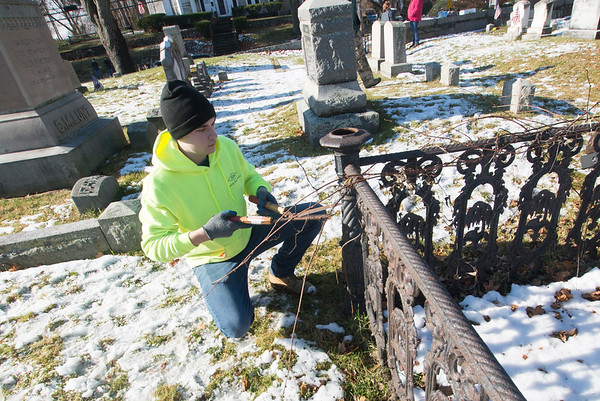 JIM VAIKNORAS/photo Eagle Scout Ryan Towne removes plants around an iron fence in the First Parish Church cemetery in Newbury Saturday morning. Towne and about 15 volunteers cut away shrubs and small trees around headstones through out the morning.