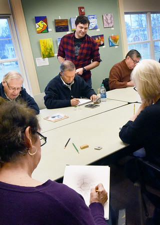 BRYAN EATON/Staff photo. Artist Andy Robinson looks over the works of participants in the newest drop-in class at the Newburyport Senior Center, Adventures in Drawing with Andy which meets on Tuesdays. Robinson whose main concentration is in children's illustration starts with basics then teaches them to look at things from different perspective as they explore different techniques and mediums.