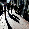 JIM VAIKNORAS/Staff photo Shoppers cast long shadows in bright sunshine as they make their way down State Street in Newburyport Friday.