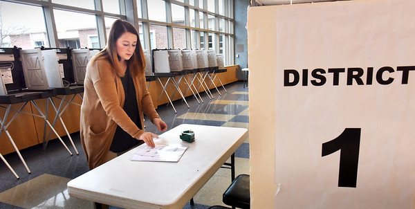 BRYAN EATON/Staff photo. Amesbury city clerks office administrative assistant Amanda Haggstrom attaches precint info at check-in tables at Amesbury High School on Monday afternoon.