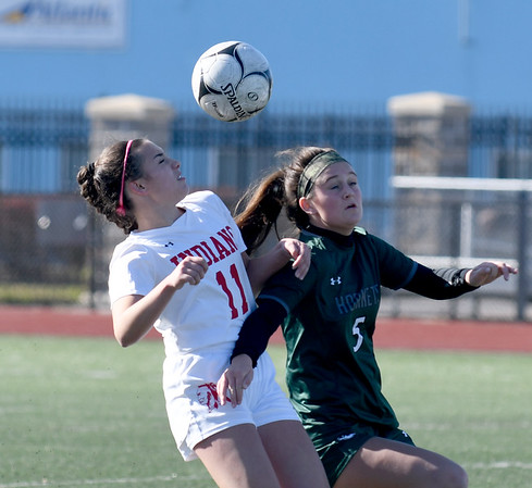 JIM VAIKNORAS/photo Amesbury'sEmma DiPietro heads the ball with Mancester-Essex player Claire O'Brien during their game at Manning Field in Lynn Sunday. Amesbury won the game 2-1 in double overtime.