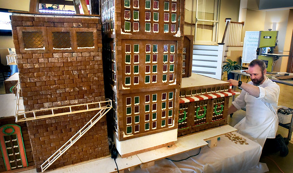 BRYAN EATON/Staff photo. Jim Shalkowski works on this year's gingerbread house Santa's North Pole Toy Factory Village.