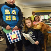 BRYAN EATON/Staff photo. Colin Goyette, 7, left, and Jasyne Dighton, 9, present birthday cards during a party for Bear, a therapy dog owned by former teacher Beth Sayre-Scibona at the Salisbury Elementary School. She brings the dog in twice a week to interact with students for relaxation and support if they're feeling down with some of the children reading to the canine.
