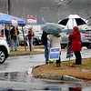 BRYAN EATON/Staff photo. Supporters of James Kelcourse, Jennifer Rocco-Runnion and others brave the rain with a tent and umbrellas at the Hilton Center in Salisbury on Tuesday afternoon.