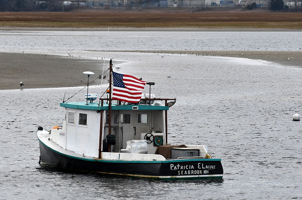 JIM VAIKNORAS/photo Tee flag waves in the stiff wind Saturday aboard the Patricia Elaine in Seabrook Harbor.
